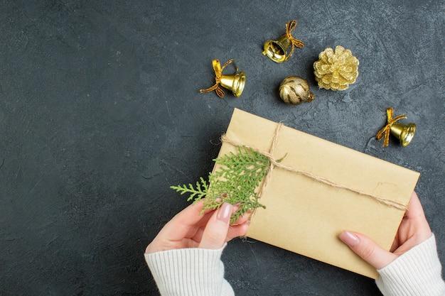 Close-up van hand met geschenkdoos en decoratie accessoires op donkere achtergrond Gratis Foto