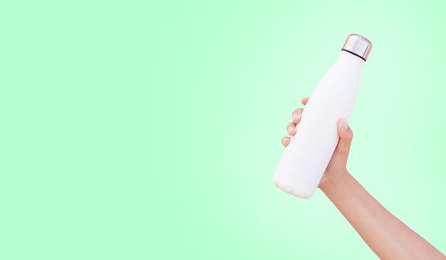 Close-up van hand met witte herbruikbare stalen thermo waterfles geïsoleerd op groene achtergrond met kopie ruimte. Premium Foto