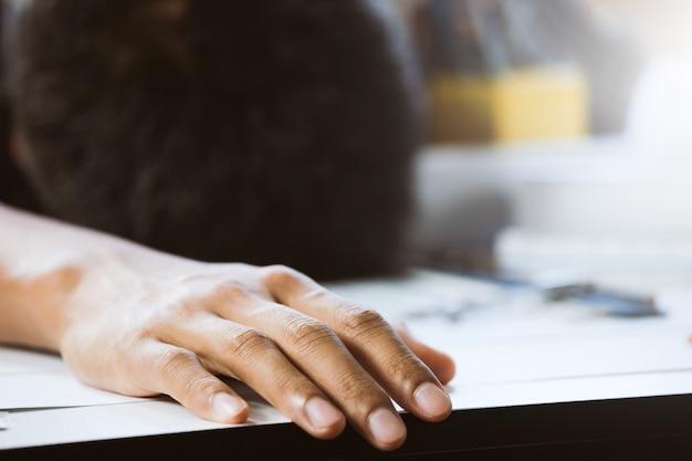 Close-up van hand zakenman met een dutje op bureau in werkruimte. concept bouwer werken aan huis project. Premium Foto