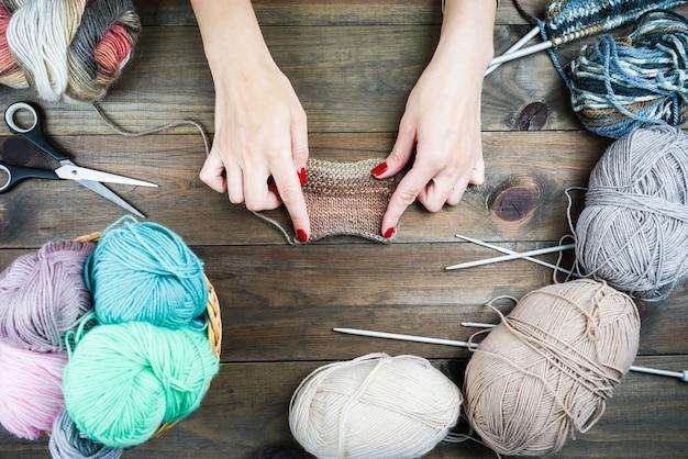 Close-up van handen breien, kleurrijke draden voor handgemaakte winterkleren. Premium Foto