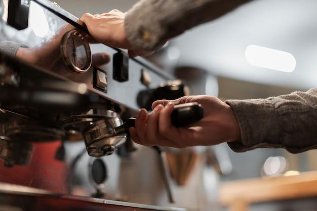 Close-up van handen die aan koffiemachine werken Gratis Foto