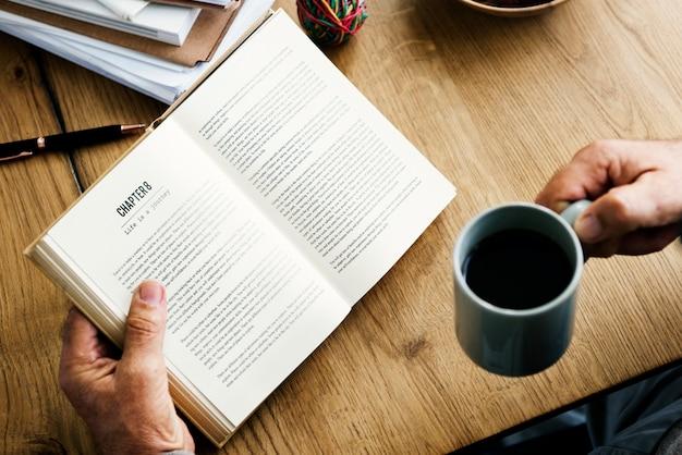 Close-up van handen met open roman en koffiekopje Gratis Foto