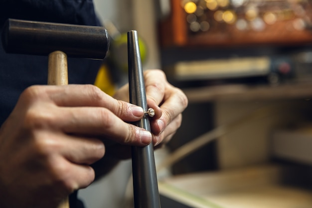 Close-up van handen van juwelier, goudsmeden maken van gouden ring met edelsteen met behulp van professionele gereedschappen Gratis Foto