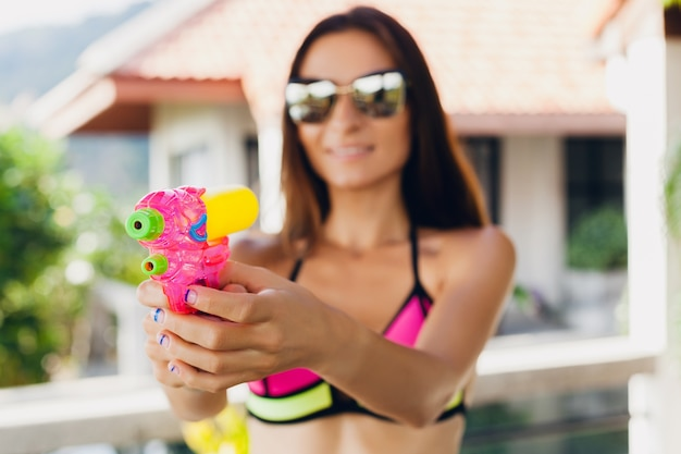 Close-up van handen van vrij lachende gelukkige vrouw spelen met watergun speelgoed bij zwembad op tropische zomervakantie op villahotel met plezier in bikini zwembroek, kleurrijke stijl, feeststemming Gratis Foto