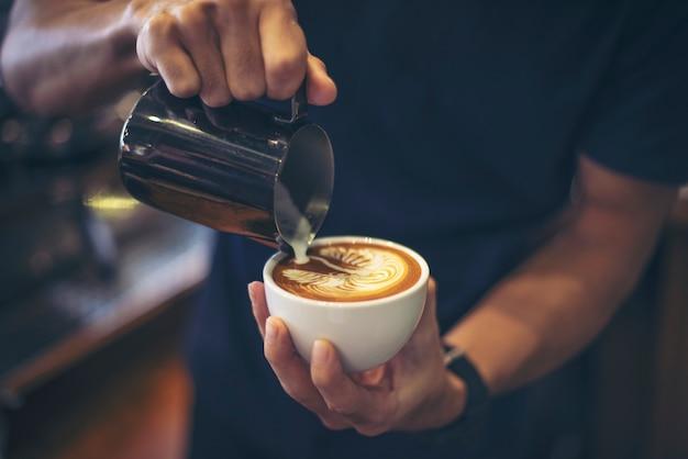 Close-up van handenbarista maakt de verf van de latte koffiekunst Gratis Foto