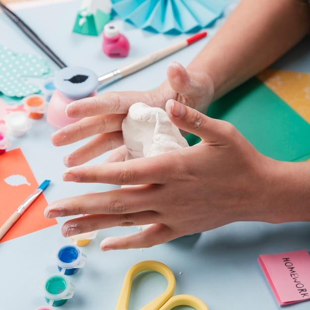 Close-up van handkneedende witte klei van craftswoman Gratis Foto