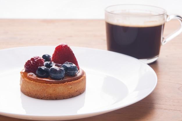 Close-up van heerlijke mini taart met bessen en kopje koffie Gratis Foto