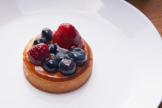 Close-up van heerlijke mini taart met bessen op plaat Gratis Foto
