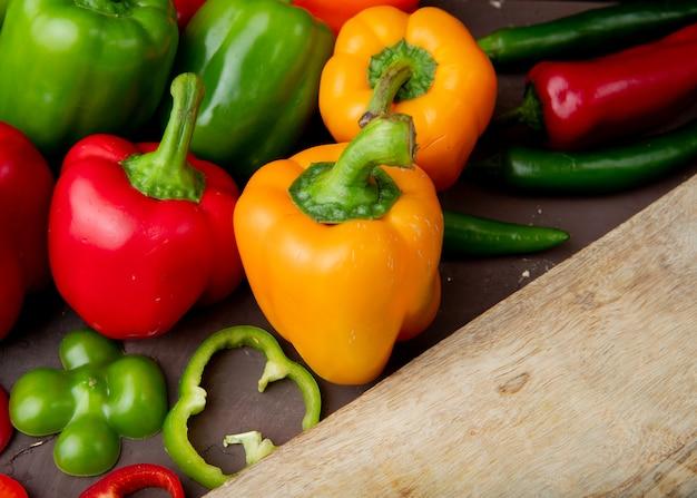 Close-up van hele en gesneden paprika's met snijplank Gratis Foto
