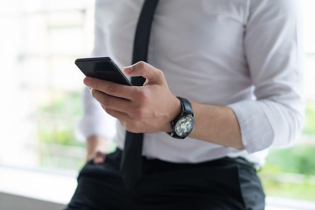 Close-up van het bedrijfsmens texting op smartphone en leunend op vensterbank Gratis Foto