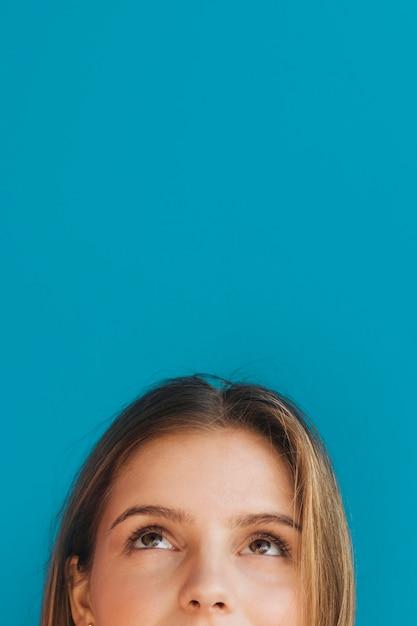 Close-up van het gezicht die van de jonge vrouw omhoog tegen blauwe achtergrond kijkt Gratis Foto