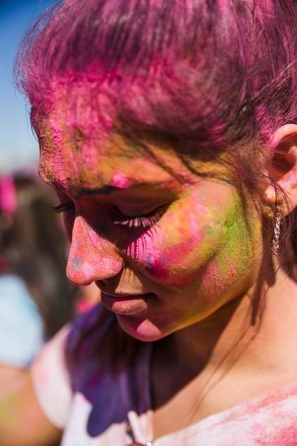 Close-up van het gezicht van een vrouw bedekt met holi kleur Gratis Foto