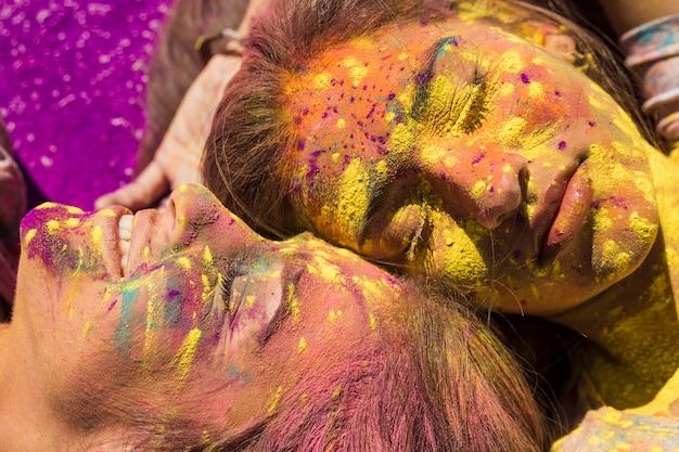 Close-up van het gezicht van jonge vrouwen bedekt met holi kleur Gratis Foto