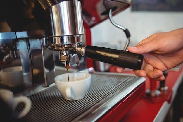 Close-up van het koffiezetapparaathandvat van de kelnersholding bij koffie Premium Foto