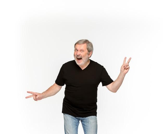 Close-up van het lichaam van de hogere man in lege zwarte t-shirt geïsoleerd op een witte achtergrond. kleding, bespotten voor ontwerpconcept met exemplaarruimte. Gratis Foto