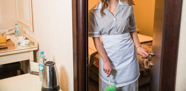 Close-up van het stofdoek van de meisjeholding ter beschikking status bij de ingang van hotelslaapkamer Gratis Foto