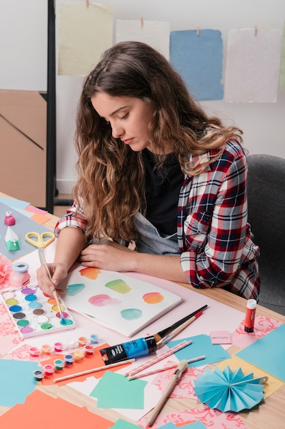 Close-up van het vrouwelijke kunstenaar schilderen op witte pagina Gratis Foto