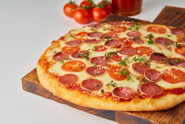 Close-up van hete zelfgemaakte italiaanse pepperoni pizza met salami, mozzarella op witte tafel, rustiek diner met worst en tomaten, zijaanzicht. Premium Foto