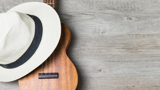 Close-up van hoed over de gitaar tegen houten achtergrond Gratis Foto