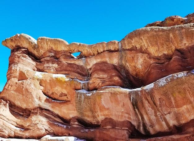Close-up van hoge rotsen in een woestijn met verbazingwekkende texturen en een blauwe hemel Gratis Foto