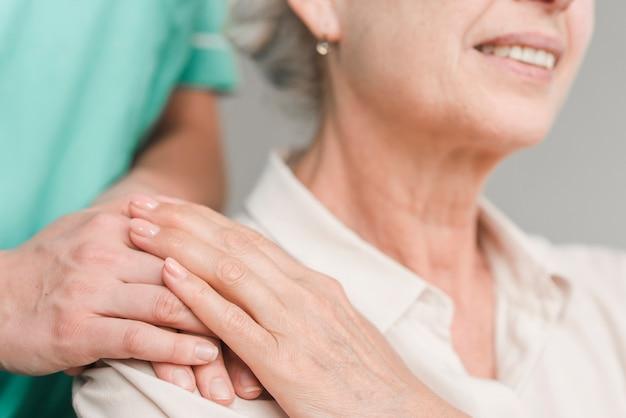Close-up van hogere vrouw wat betreft verpleegstershand Gratis Foto