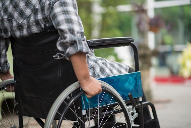 Close-up van hogere vrouwenhand op wiel van rolstoel tijdens gang in het ziekenhuis Gratis Foto
