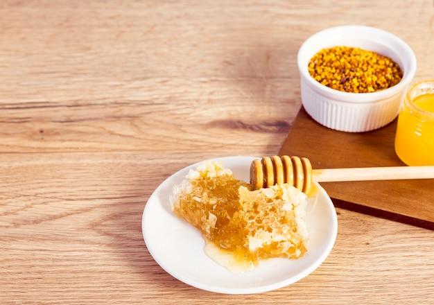 Close-up van honingraat en bijenstuifmeel op houten bureau Gratis Foto