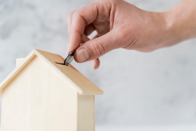 Close-up van iemands hand invoegen van de munt in de houten huis spaarpot Gratis Foto