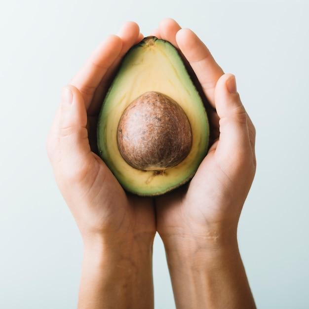 Close-up van iemands hand met avocado Gratis Foto