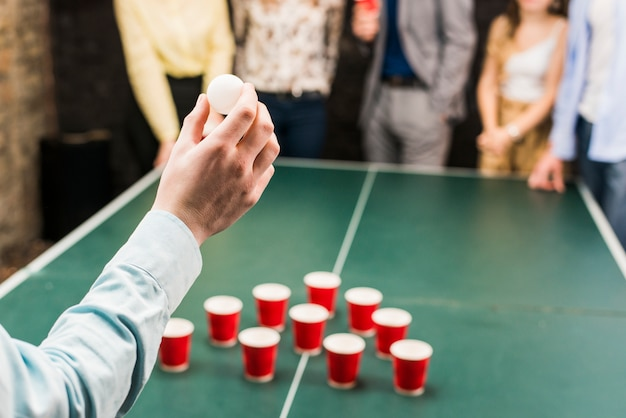 Close-up van iemands hand met bal voor bier pong spel Gratis Foto