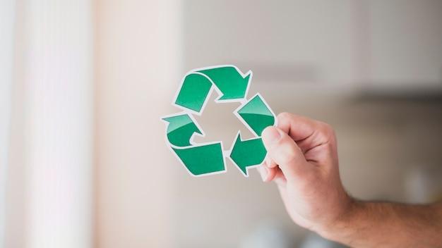 Close-up van iemands hand met groene recycle pictogram Gratis Foto