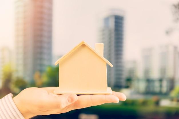 Close-up van iemands hand met houten huis model tegen de skyline van de stad Gratis Foto