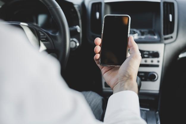 Close-up van iemands hand met mobiele telefoon met leeg scherm in de auto Gratis Foto