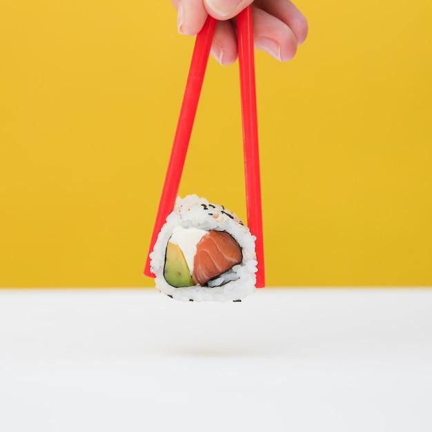 Close-up van iemands hand met sushi met rode stokjes tegen gele achtergrond Gratis Foto