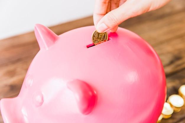 Close-up van iemands hand spaar munt in roze spaarpot Gratis Foto