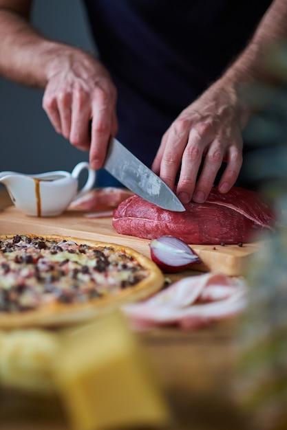 Close-up van iemands handen gesneden rundvlees met mes aan boord. sauskom, halve ui en gekookte pizza ook op tafel. Premium Foto