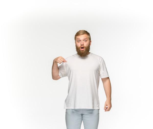 Close-up van jong man lichaam in lege witte t-shirt die op witte ruimte wordt geïsoleerd. bespotten voor ontwerpconcept Gratis Foto