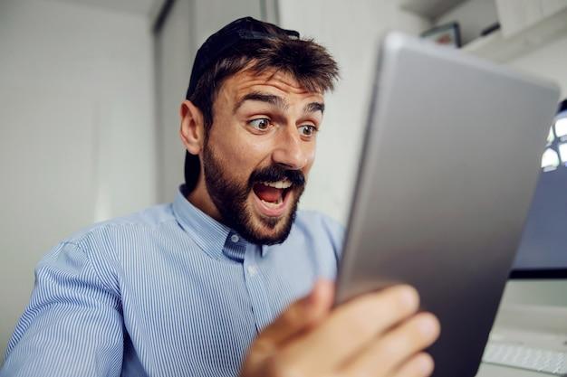 Close-up van jonge aantrekkelijke bebaarde man gekleed business casual kijken naar tablet. Premium Foto