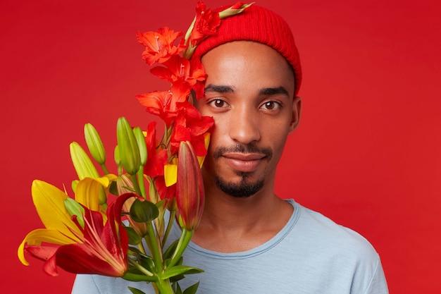 Close up van jonge aantrekkelijke man in rode hoed en blauw t-shirt, houdt een boeket in zijn handen, kijkt naar de camera met kalmerende uitdrukking en glimlachen, staat over rode achtergrondgeluid. Gratis Foto