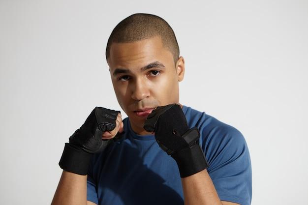 Close up van jonge donkere mannelijke bokser stijlvolle zwarte bokshandschoenen dragen tijdens het trainen in de studio, vaardigheden oefenen en stoten beheersen, met ernstige geconcentreerde gezichtsuitdrukking Gratis Foto