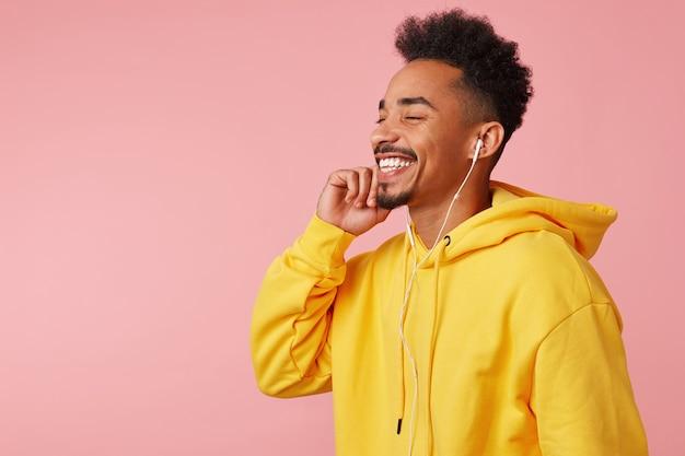 Close up van jonge gelukkig afro-amerikaanse man in gele hoodie, genietend van cool nieuw lied van zijn favoriete band op koptelefoon, staande met gesloten ogen en breed lachend. Gratis Foto