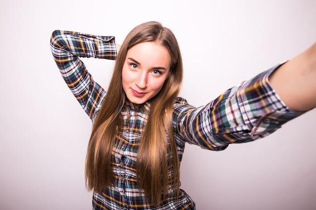 Close-up van jonge mooie vrouw die selfie. geïsoleerde witte muur Gratis Foto