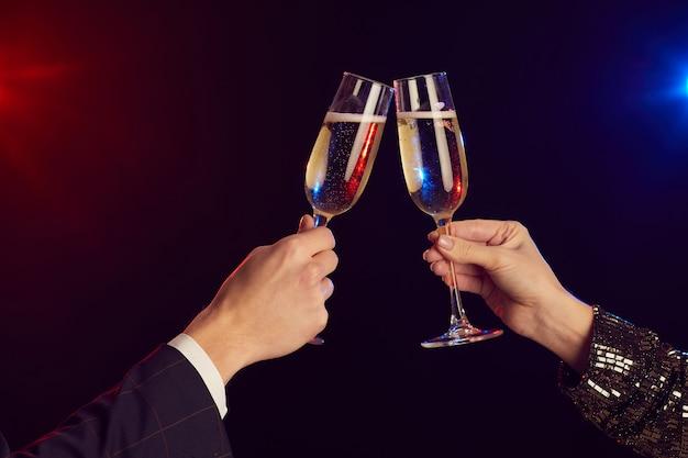 Close-up van jonge paar rammelende champagneglazen verlicht door feestverlichting tegen zwarte achtergrond geschoten met flits Premium Foto