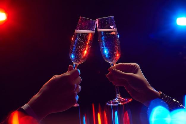 Close up van jonge paar rammelende champagneglazen verlicht door feestverlichting tegen zwarte achtergrond, kopieer ruimte Premium Foto