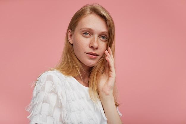 Close-up van jonge peinzende aantrekkelijke roodharige vrouw met natuurlijke make-up zacht haar gezicht aan te raken met opgeheven hand en camera te kijken met kalm gezicht, geïsoleerd op roze achtergrond Gratis Foto