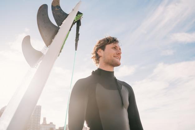Close-up van jonge surfer die zich naast zijn surfplank op het strand bevindt. sport en watersport concept. Gratis Foto