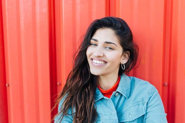 Close-up van jonge vrouw die camerazitting tegen rode metaalachtergrond bekijkt Gratis Foto