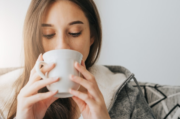 Close-up van jonge vrouw dragen trui koffie of thee nippen uit witte mok in de ochtend Premium Foto