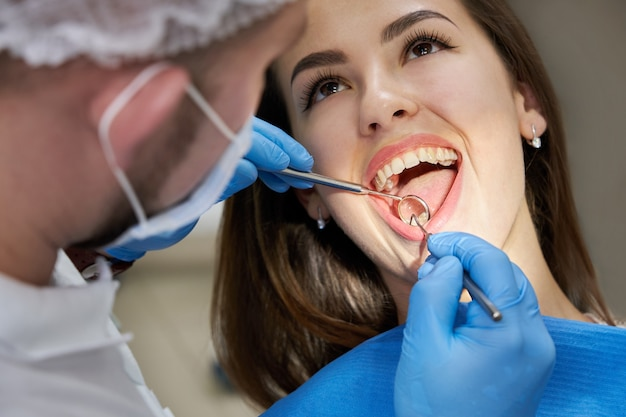 Close up van jonge vrouw met tandheelkundige check-up in tandartspraktijk. tandarts die een geduldig gebit met tandhulpmiddelen onderzoekt Premium Foto