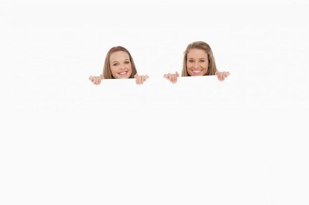 Close-up van jonge vrouwen achter een leeg teken Premium Foto